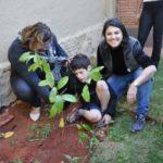 Sonia Paro e Mayda, ajudando Pietro a plantar sua muda de fruta do conde.