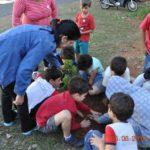 A coordenadora Luciana, orientando os alunos como plantar as mudas de árvores.