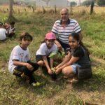 Secretário do Meio Ambiente de Monte Alto, orientando os alunos Hector, Lauane e Vitória, como plantarem a muda de árvore frutífera.